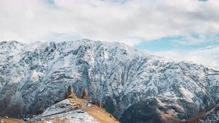 склон холма : Stepantsminda, Gergeti, Georgia. Famous Gergeti Trinity Tsminda Sameba Church In Early Winter Landscape. Beautiful Georgian Landscape In Early Winter