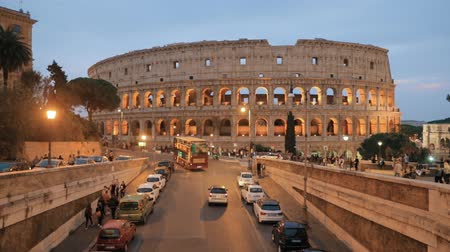 flavian : Rome, Italy. Colosseum Also Known As Flavian Amphitheatre. Traffic In Rome Near Famous World Landmark In Evening Time