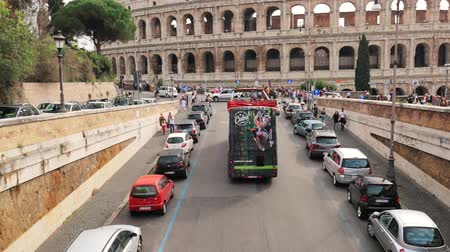 Řím : Rome, Italy - October 21, 2018: Colosseum. Red Hop On Hop Off Touristic Bus For Sightseeing In Street Near Flavian Amphitheatre. Famous World UNESCO Landmark. City Sightseeing Tour. slow motion.