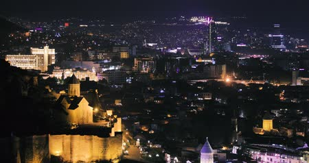 Грузия : Tbilisi, Georgia. Top View Of Narikala Fortress Amd Modern Skyscraper In Autumn Night. Georgian Capital Skyline Cityscape Стоковые видеозаписи