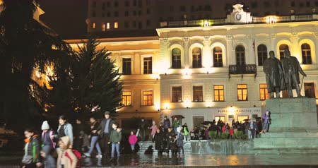 gramatika : Tbilisi, Georgia - November 22, 2018: Children and parents leave the building of the Tbilisi Classical Grammar School in autumn evening. 1st Tiflis Gymnasium and statue of Chavchavadze and Tsereteli Dostupné videozáznamy