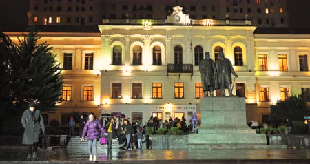 Tbilisi, Georgia - November 22, 2018: Children and parents leave the building of the Tbilisi Classical Grammar School in autumn evening. 1st Tiflis Gymnasium and statue of Chavchavadze and Tsereteli Stok Video
