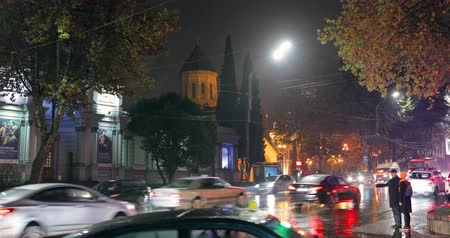 Tbilisi, Georgia - November 22, 2018: Traffic In Night Rustaveli Avenue Street. Night View Of Kashveti Church Of St. George, White Georgian Orthodox Church. Young Couple People Taking Taxi Stock Footage