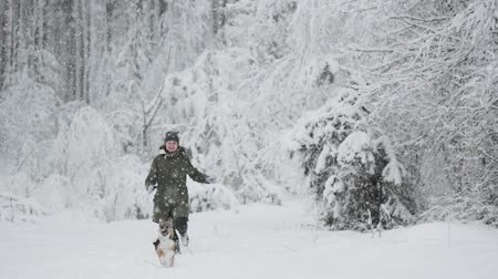 závěj : Young Beautiful Caucasian Girl Woman Dressed In Jacket Playing With Puppy Of Mixed Breed Dog In Winter Forest In Snowy Day. Girl And Dog Running Together In Forest Slo-mo Slow Motion Slow-mo Dostupné videozáznamy