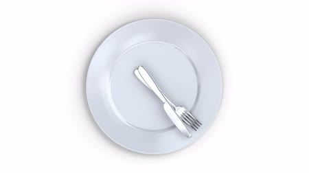 mutfak malzemesi : Healthy lifestyle concept. a plate with a clock. its time to eat. White plate with knife and fork as a watch hand view from above Stok Video