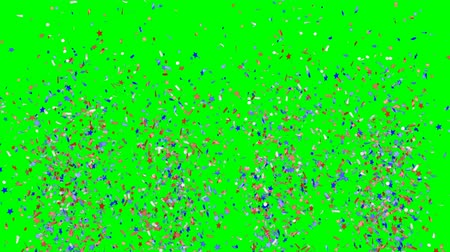 Blue, red and white festive confetti explosions falling down on a green background. Slow motion footage.