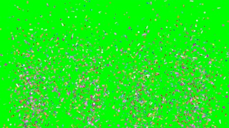 Multicolored festive confetti explosions falling on a green background. Slow motion footage.