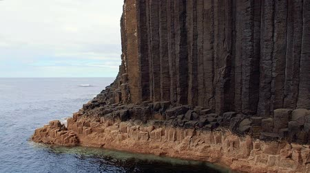 Close-up of vertical basalt columns of Fingals Cave on Staffa Island, west of Isle of Mull in Scotland. Calm waves touching the rocks. Steady shot in high frame rate. Stock Footage