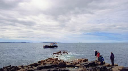 People are staying on volcanic rocks and watching a sailing boat. Group of tourists looking at ship passing by close to the shore of Staffa Island, near famous Fingals Cave with basalt columns.