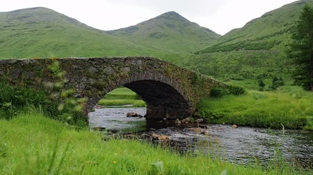 Views of Butterbridge crossing Kinglas Water, the old small arch bridge near Loch Lomond National Park, Scotland. Mountain river flows through the green valley. Steady shot and panning close-up scenes
