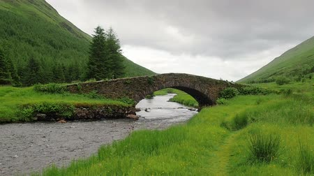 View of the stone bridge called Butterbridge in the Highlands of Scotland. Old arch bridge crossing Kinglas Water near Loch Lomond National Park. Mountain river flows through the green valley. Stock Footage