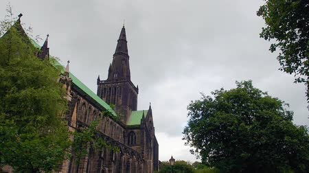 Grey clouds moving over the Glasgow Cathedral, also called the High Kirk of Glasgow, in Scotland. Green leaves shaking on a windy summer day. Steady shot in real time.