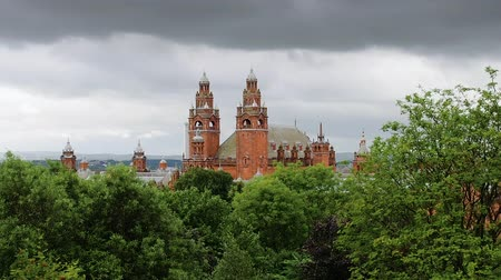 Glasgow skyline with the Kelvingrove Art Gallery, built in 1901, is partly visible above the treetops of Kelvingrove Park. Dark clouds moving fast in the sky and leaves shaking due to the strong wind.