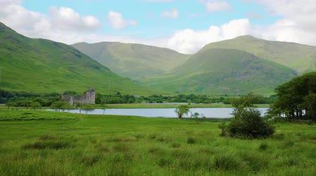lakes of scotland : Landscape time lapse view of Kilchurn Castle in Scotland. Clouds moving rapidly over the mountains and cast their shadows on the hillside. Loch Awe and trees are visible in the background.