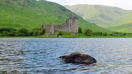 argyll : View of the famous Kilchurn Castle ruins from the other side of Loch Awe in Scotland. Big stone is visible in the lake as water ripples moving fast from left to right. Steady shot in high frame rate. Stock Footage