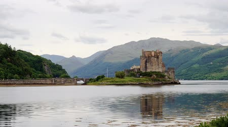 Stunning view to the famous medieval castle in Scottish Highlands reflecting in the waters of Loch Duich on a cloudy summer day. People crossing the arch bridge are visible in the background.