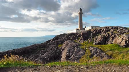 White and grey clouds passing over the historic Ardnamurchan Lighthouse in Western Scotland on a summer day. Black rocks, blue ocean and distant islands are visible. Low angle shot from the ground.