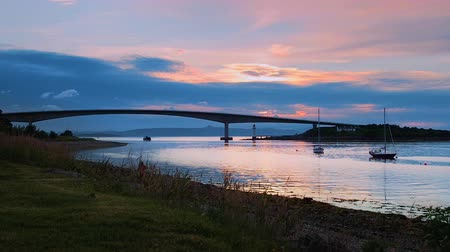 Time lapse view of Skye Bridge with normal speed at the end of the clip. Red and blue sunset skies over the tranquil harbour in Kalyakin, Isle of Skye in Western Scotland. Idyllic summer evening.