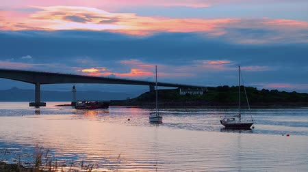 Amazing view of Skye Bridge and a ship passing bt. Red and blue sunset skies over the tranquil harbour in Kalyakin, Isle of Skye in Western Scotland. Idyllic summer evening. Stock Footage