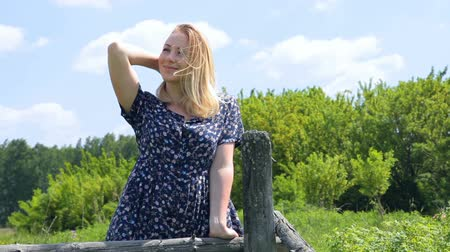 blond girl smiling on the summer landscape . Positive human emotion facial expression feelings