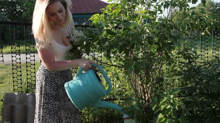 Young woman watering a summer garden