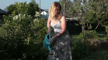 Woman in garden watering flowers