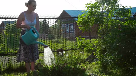 Happy Female Gardener Waters Plants and Flowers with a watering can in Sunny Garden. Stock mozgókép