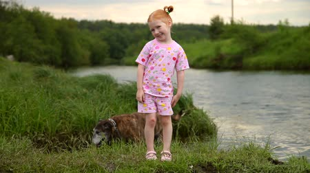 Red-Haired Girl Walking With a Dog on the River. Smile on camera