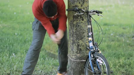 кража : Thief trying to break the bicycle Lock with ax