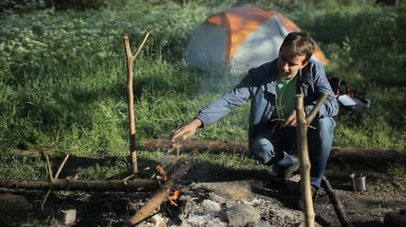 выживание : Man throws wood on the fire in the camping. Early morning in the forest