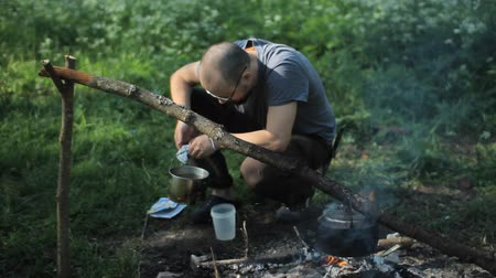 выживание : Man pours boiling water near the fire. On the bright fire hot kettle Стоковые видеозаписи