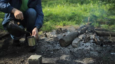 выживание : Man pours tea from a pot into a metal cup. Near the fire burns, the early morning in the forest