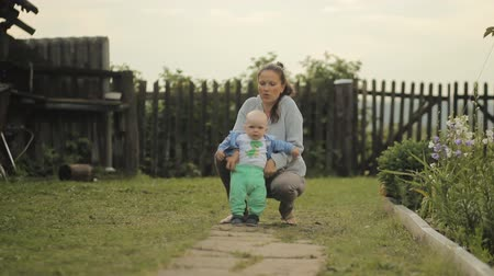 step : Beautiful baby takes its first steps with his mother. They go down the path cottage Stock Footage
