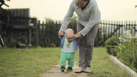 lépések : Beautiful baby takes its first steps with his mother. They go down the path cottage Stock mozgókép