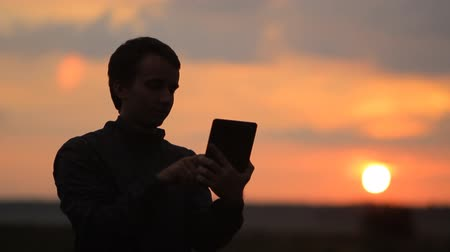 telefone celular : The man touches the tablet. Beautiful sunset on the background Stock Footage