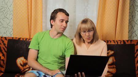 компания : Adult male teaches old woman making video call on laptop. Mother and son smiling and sitting on a sofa at home