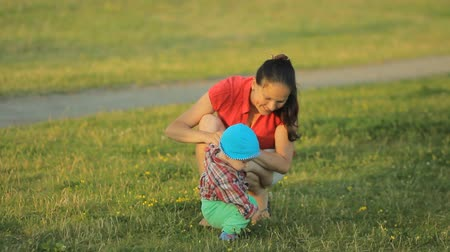 pozitivity : Mom playing with baby son in the park. The child makes the first steps