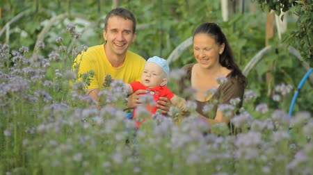 lupine : Young mother and father holding her newborn baby in a purple flower field