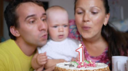 jovial : Beautiful baby celebrates first birthday. Young mother and father to help blow out the candle on the cake