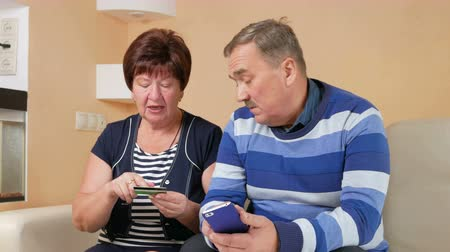 elliler : Senior couple shopping in internet shop by credit card and phone. Man and woman sitting at home data card are administered carefully on the couch