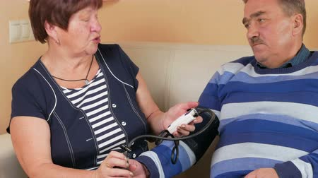 sphygmomanometer : Elderly woman measures the blood pressure at home on the couch. Poor mans well-being. Taking care of his wife about her husband