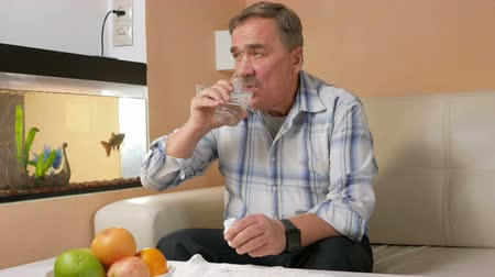 болеутоляющее : Senior man mustache taking pills at home, and drinks a glass of water. He sits on the couch near the aquarium and improves their health Стоковые видеозаписи