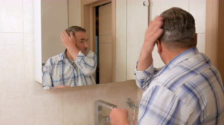 cabelos grisalhos : Senior man straightens her hair in the bath. He looks in the mirror and carefully inspects the hair. The concept of self-care