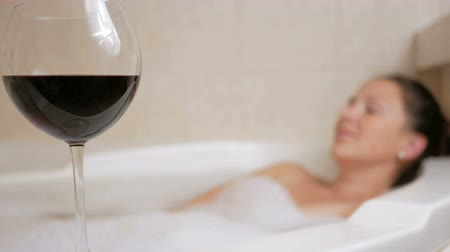 koupat se : Beautiful girl taking a bubble bath with a glass of wine. A large white bath and joy on his face. relaxation concept