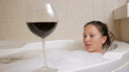 hot tub : Beautiful girl taking a bubble bath with a glass of wine. A large white bath and joy on his face. relaxation concept