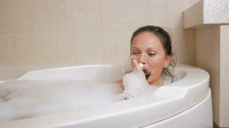 пузыри : Beautiful girl taking a bubble bath with a glass of wine. A large white bath and joy on his face. relaxation concept