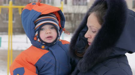 rüzgârla oluşan kar yığını : Baby in his mothers arms in the park in winter. They warmly dressed, mother talking to her son. Handsome boy about a year. Winter lifestyle concept.