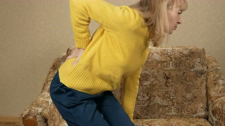 painéis : Women age can not climb off the couch because of the pain in the back in house. She sits back and makes a lumbar massage Stock Footage