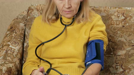 take blood : Woman aged measures the pressure of their own home on the couch. She listens to pulse through sphygmomanometer