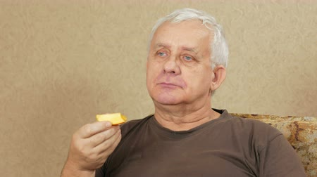man eating : Man aged overweight eats fruit at home on the couch. He cut off a piece of persimmon and makes a few bites. Healthy food concept